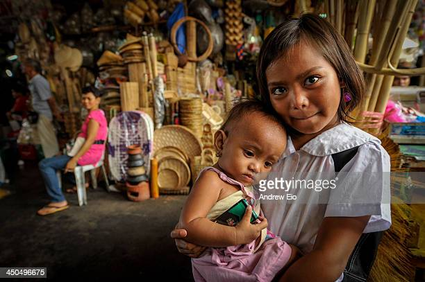 Young Philippino schoolgirl in a white shirt holding her younger sister in front of a typical street market selling all types of wicker ware and...