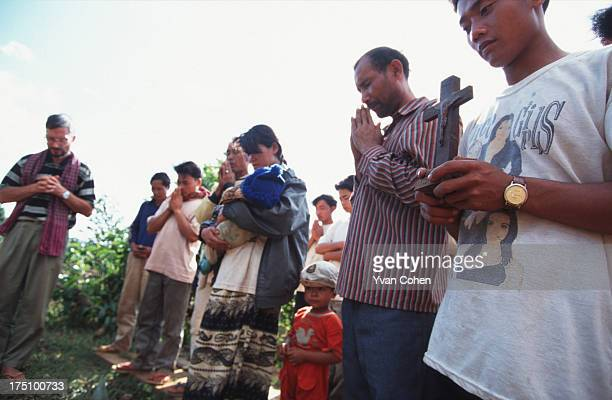 BOUSRA MONDOLKIRI CAMBODIA A young Phnong montagnard carries a crucifix during a prayer to bless a forthcoming journey Traditionally animist a small...