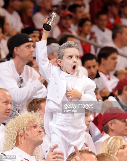 A young Phoenix Coyotes fan holds up a small Stanley Cup Trophy while cheering on the Coyotes against the Detroit Red Wings in Game One of the...