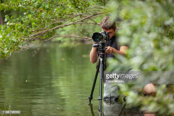 jeune photographe capturant une image d'une position inconfortable au milieu de la rivière - thème de la photographie photos et images de collection