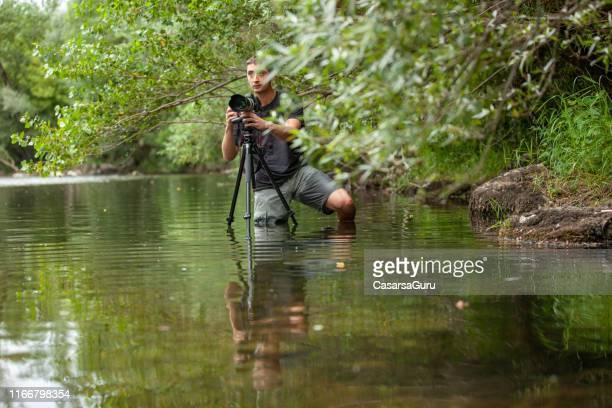 川の真ん中の不快な位置から画像を撮影する若い写真家 - ルポルタージュ ストックフォトと画像