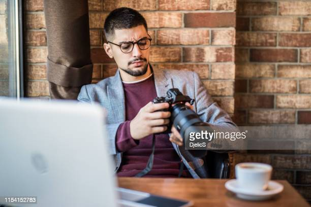 young photographer checking photos  while working in coffee shop. - digital camera stock pictures, royalty-free photos & images