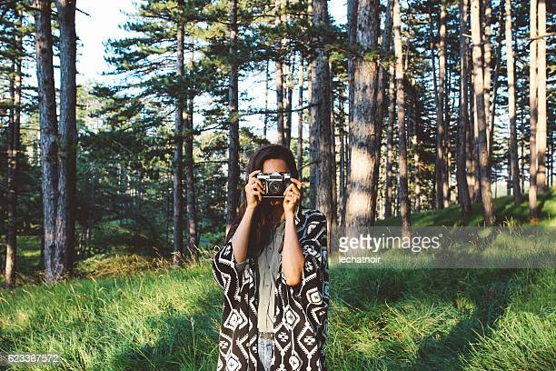 Young photographer woman in the woods
