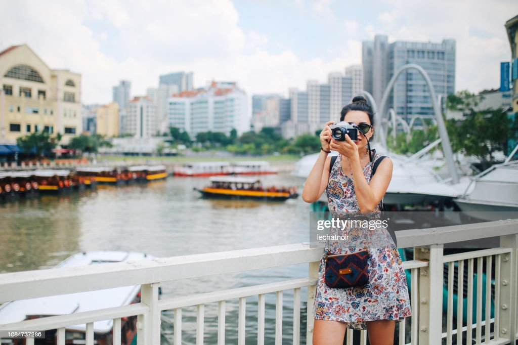 young photographer woman taking images in Singapore : Stock Photo