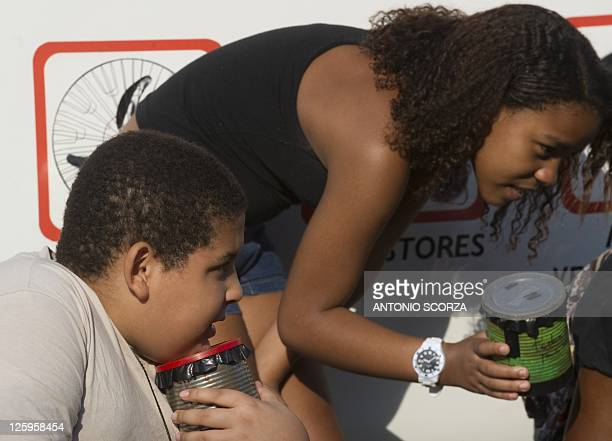 Young photography students Jonatan Castro and Jenifer Martins prepares their pin hole cameras during a street class at the favela da Mare shantytown...
