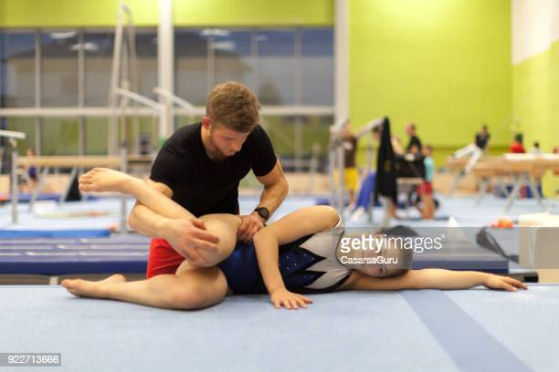 Young Physical Therapist Giving Therapy to a Teenage Gymnastics Athlete