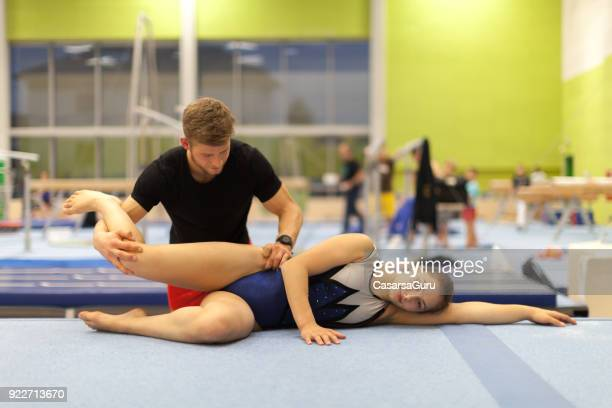 young physical therapist giving therapy to a teenage gymnastics athlete - daily sport girls stock pictures, royalty-free photos & images