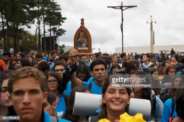 A young pilgrim holds an image of the Virgin Mary as they arrive at the Sanctuary of Fatima on May 12 2017 in Fatima Portugal Pope Francis will be...