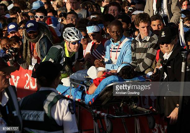 A young pilgrim is taken away by St John's Ambulance at the Papal Welcome Ceremony at Barangaroo on Sydney Harbour on July 17 2008 in Sydney...