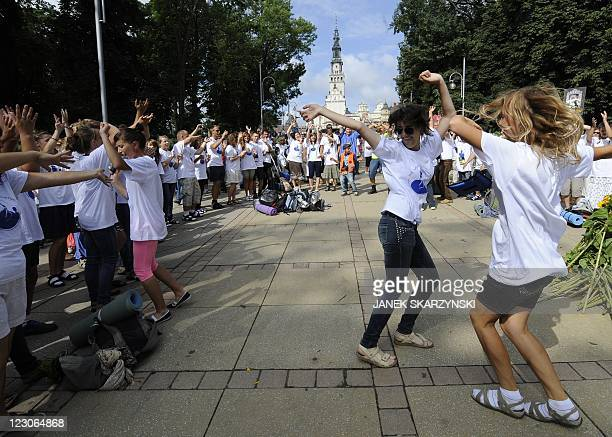 Young piligrims dance as they wait to enter the Marian shrine of Czestochowa on August 14 2011 in southern Poland For 300 years thousands of pilgrims...