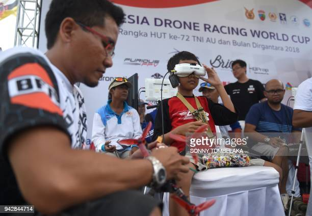 A young pilot adjusts his FPV headset goggles as he prepares to race his drone during the FAI Drone Racing World Cup event in Denpasar on Indonesia's...
