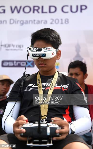 A young pilot controls his race drone during the FAI Drone Racing World Cup event in Denpasar on Indonesia's resort island of Bali on April 7 2018 /...