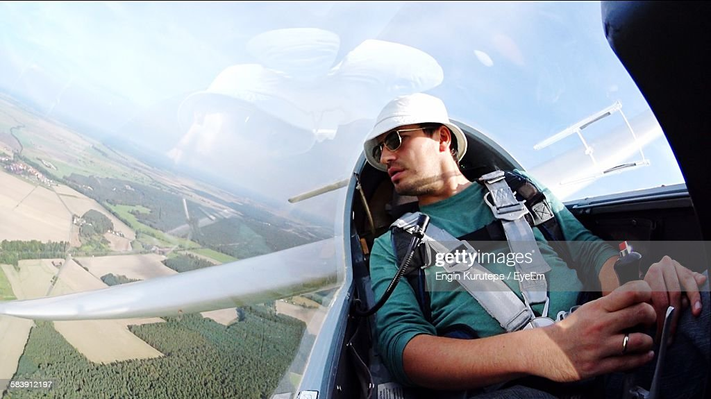 Young Pilot Flying Glider Airplane Over Landscape Against Sky : Stock Photo