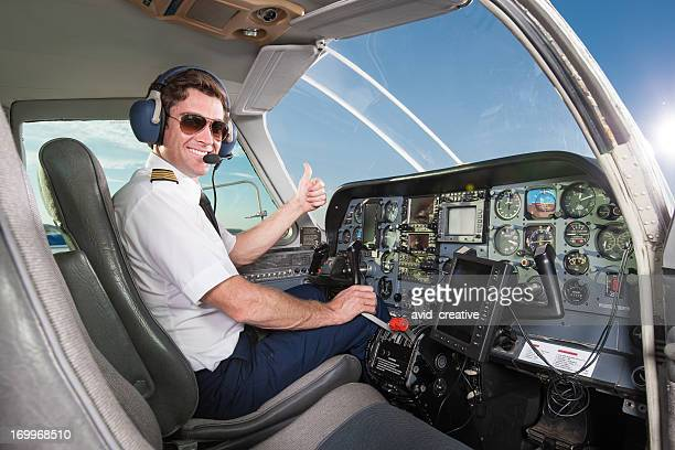 Young pilot in aircraft cockpit giving thumbs up