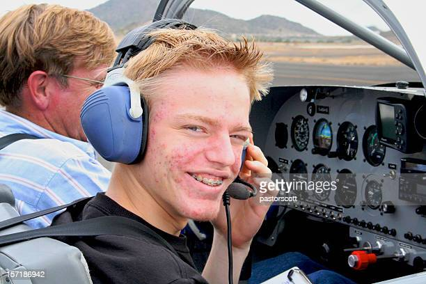 Young pilot in training sitting in a cockpit with instructor