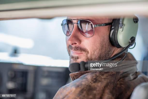 Young pilot sitting in cockpit, portrait