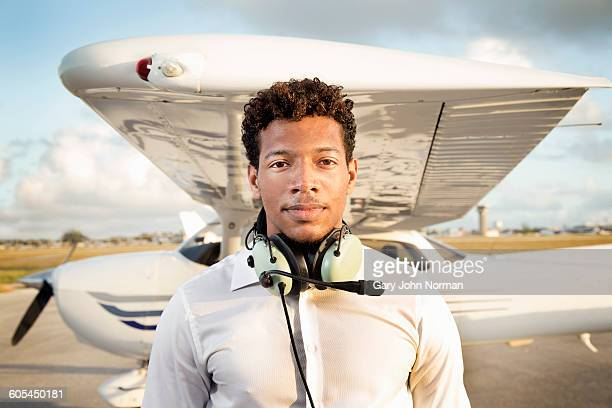 Young pilot standing in front of his plane