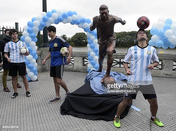 Young play with footballs next to a sculpture of Argentina's forward Lionel Messi after it unveiling by Buenos Aires Mayor Horacio Rodriguez Larreta...
