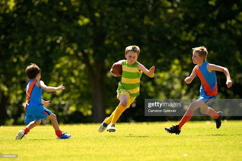 Young player avoids a tackle in a football game : Stock Photo