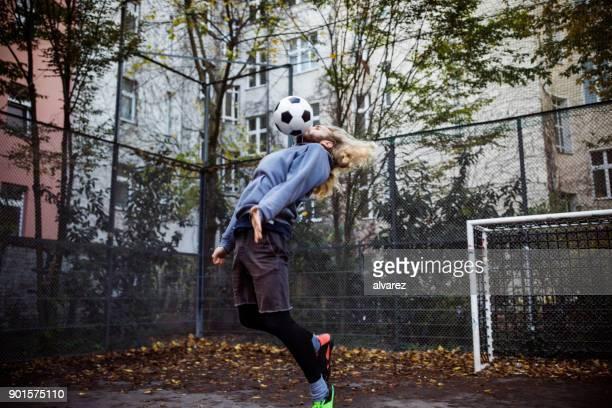 若い選手の胸でサッカー ボールをブロック