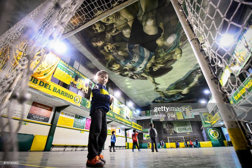 A young player guards the net at Sportivo Pereyra de Barracas club on June 13, 2018 in Buenos Aires, Argentina. The mural was painted in the ceiling of the pitch by local artist Santiago Barbeito depiciting the 'Creation of Adam' and making a tribute to Argentin football stars.