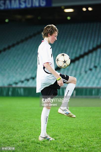 A young player joins Singer Brian McFadden on the field at the launch of new Fox8 TV show 'Football Superstar' at Sydney Football Stadium on June 18...