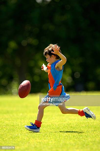 young player kicking australian football - australian rules football stock-fotos und bilder