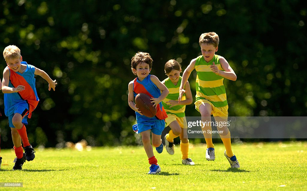 Young player running from his opposition : Stock Photo