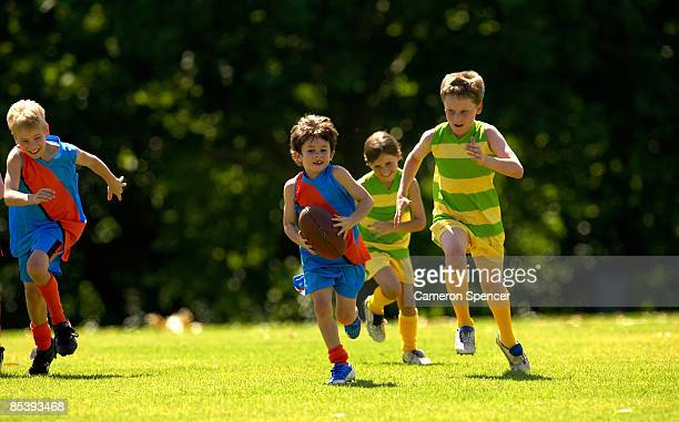 young player running from his opposition - afl stock pictures, royalty-free photos & images