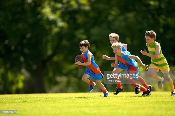 young player running from opposition with ball - afl stock pictures, royalty-free photos & images