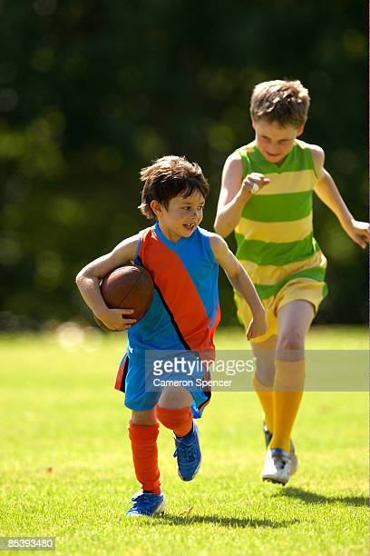 Young player runs from opposition in football game