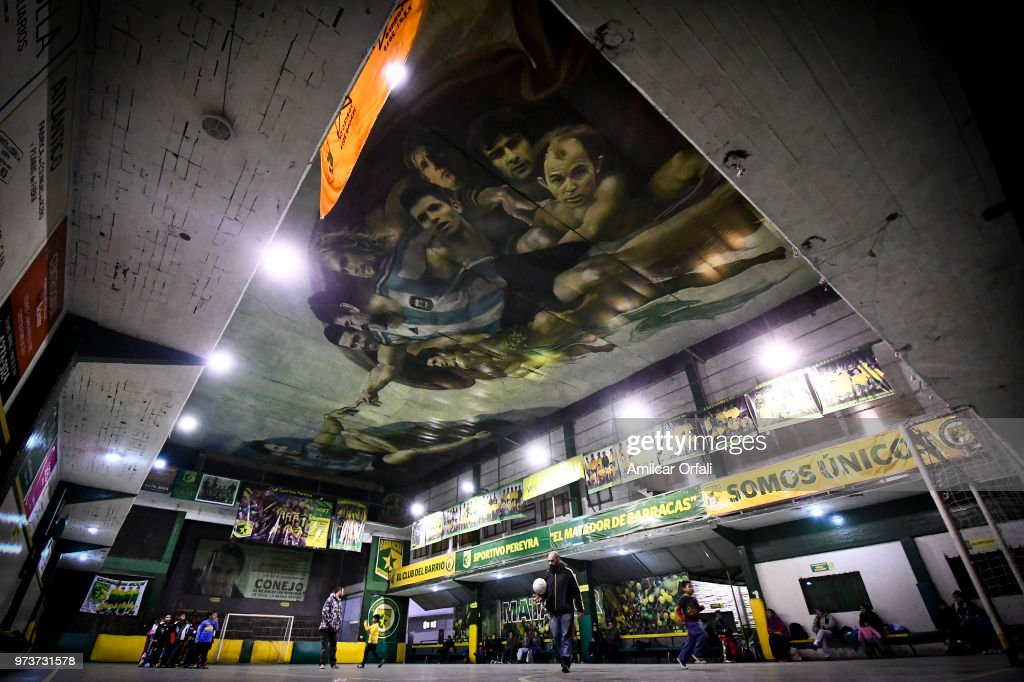 Young players practice at Sportivo Pereyra de Barracas Club on June 13, 2018 in Buenos Aires, Argentina. The mural was painted in the ceiling of the pitch by local artist Santiago Barbeito depiciting the 'Creation of Adam' and making a tribute to Argentin football stars.