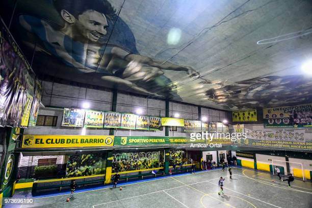 Young players run during a soccer match at Sportivo Pereyra de Barracas Club on June 13 2018 in Buenos Aires Argentina The mural was painted in the...