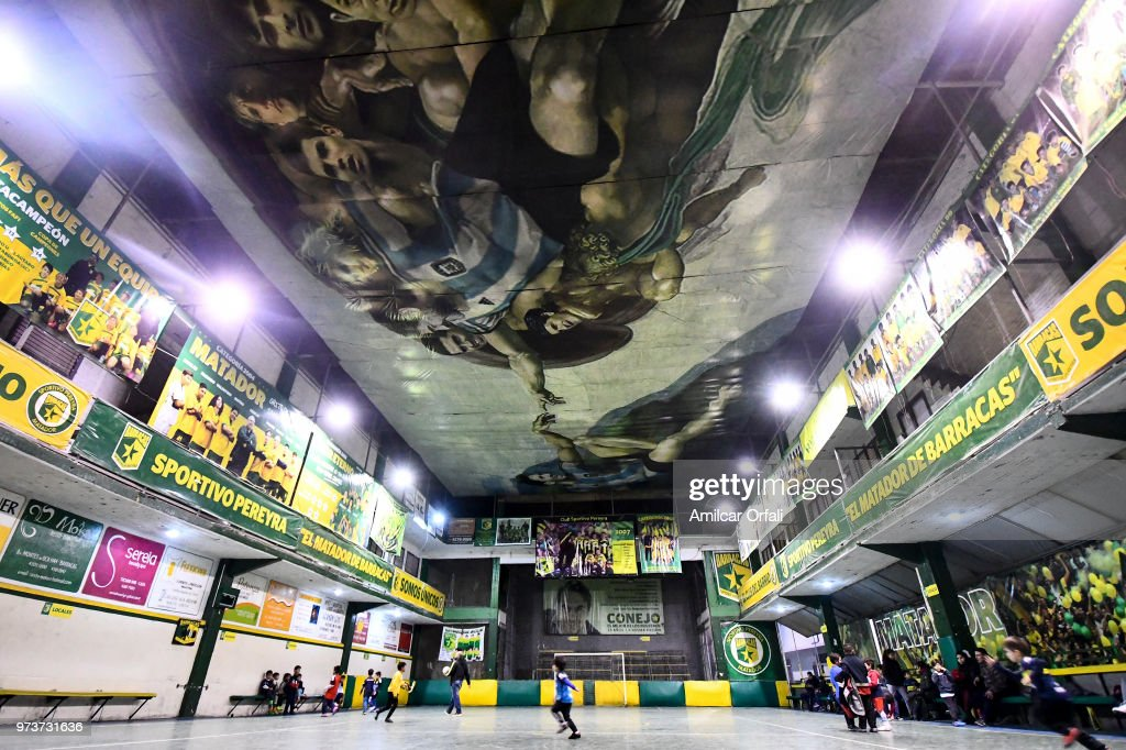 Young players run during a soccer match at Sportivo Pereyra de Barracas Club on June 13, 2018 in Buenos Aires, Argentina. The mural was painted in the ceiling of the pitch by local artist Santiago Barbeito depiciting the 'Creation of Adam' and making a tribute to Argentin football stars.