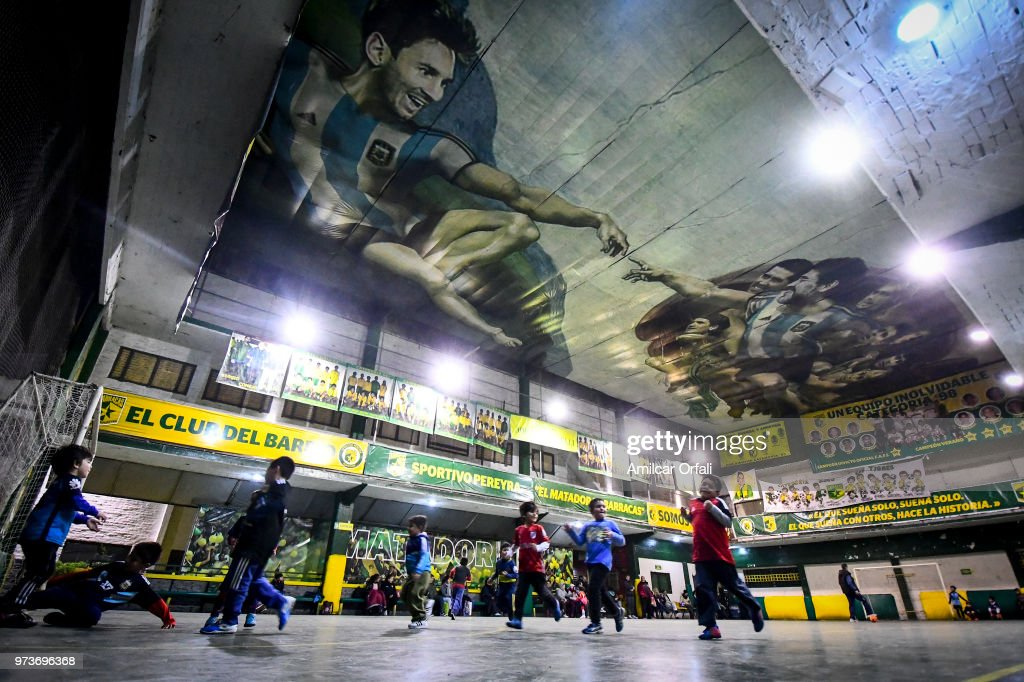 Young players run suring a soccer match at Sportivo Pereyra de Barracas Club on June 13, 2018 in Buenos Aires, Argentina. The mural was painted in the ceiling of the pitch by local artist Santiago Barbeito depiciting the 'Creation of Adam' and making a tribute to Argentin football stars.