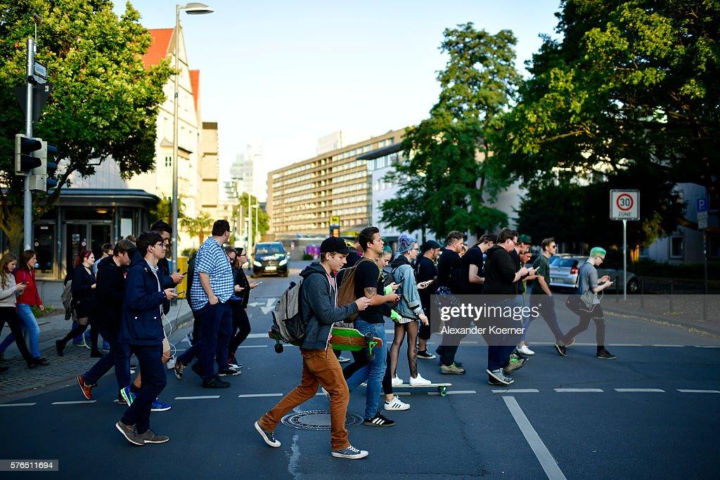 Young players walk through the city centre of Hanover while holding their smartphones and playing 'Pokemon Go' on July 15, 2016 in Hanover, Germany. 1.200 players have participated in the night walk through the city centre until midnight. 'Pokemon Go' is a mobile game for smartphones, it uses advanced reality and geo-data to integrate the player in his search for new monsters or opponents within his location. The player now has to walk through the city, instead of spending time in front of a computer.