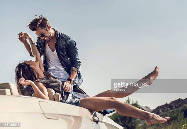 Young playful couple having fun together on convertible car.