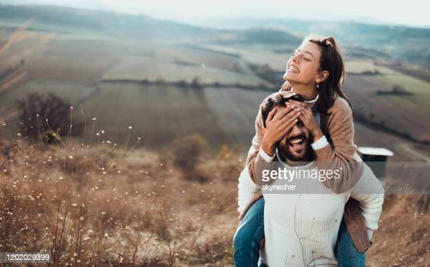young playful couple having fun while piggybacking in autumn day on a hill. - hands covering eyes stock pictures, royalty-free photos & images