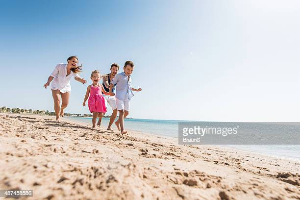 Young playful family chasing on the beach during summer day.