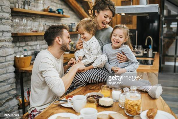 young playful family having fun during breakfast in the kitchen. - famiglia con due figli foto e immagini stock