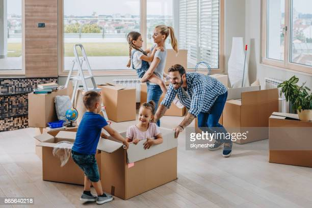 young playful family having fun while moving in new penthouse. - penthouse girls stock pictures, royalty-free photos & images