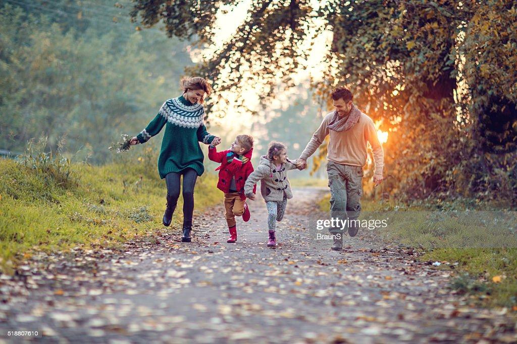 Joven familia juguetón divirtiéndose mientras corriendo en el parque. : Foto de stock