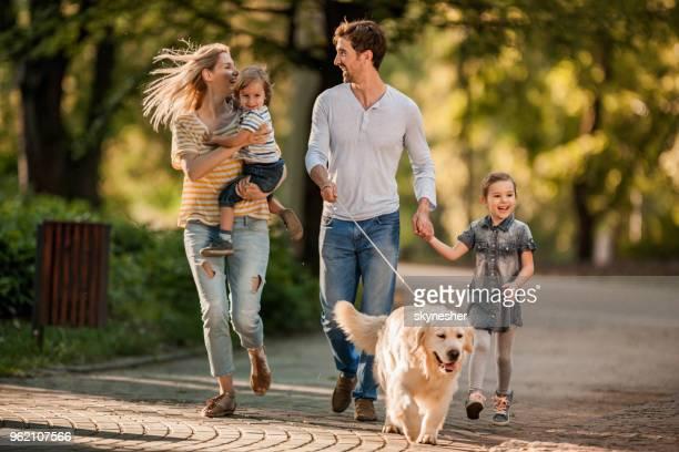 Joven juguetona familia corriendo con su perro perdiguero de oro durante la primavera en el parque.