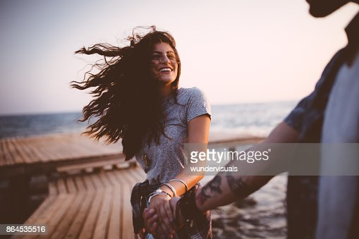 Young playful hipster couple holding hands on jetty at sunset