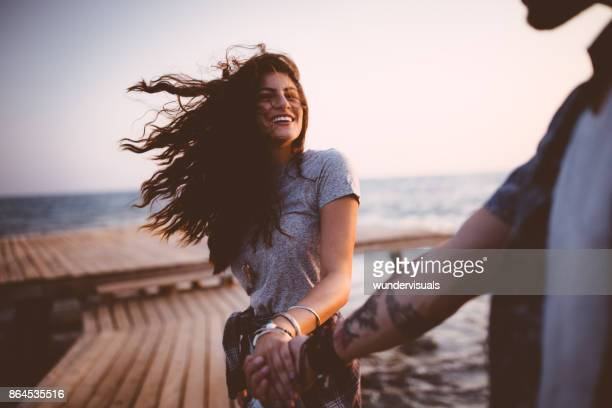 young playful hipster couple holding hands on jetty at sunset - couples stock pictures, royalty-free photos & images