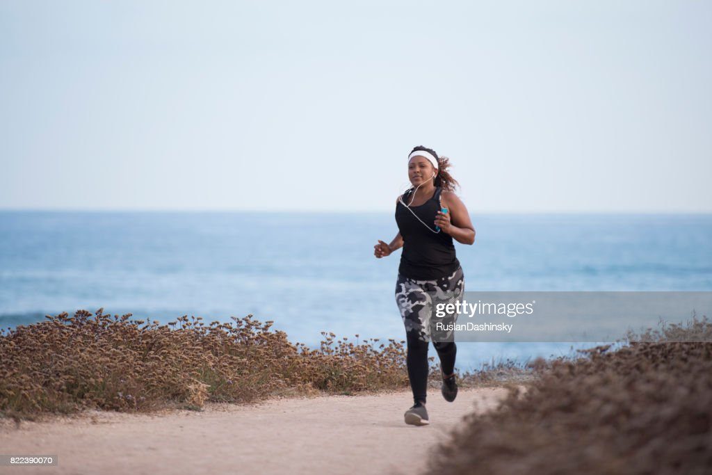 Young plump woman running outdoors along the seacoast. : Stock Photo