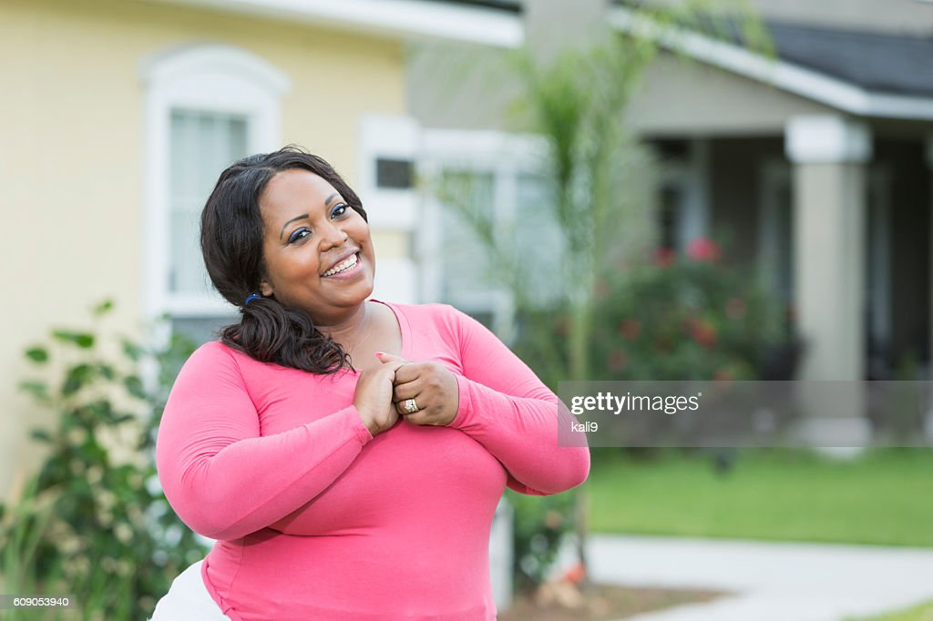 Young, plus size African American woman outside house : Stock Photo