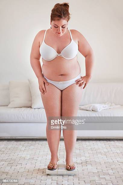 young plus-size woman on scale in lounge - chubby stock photos and pictures