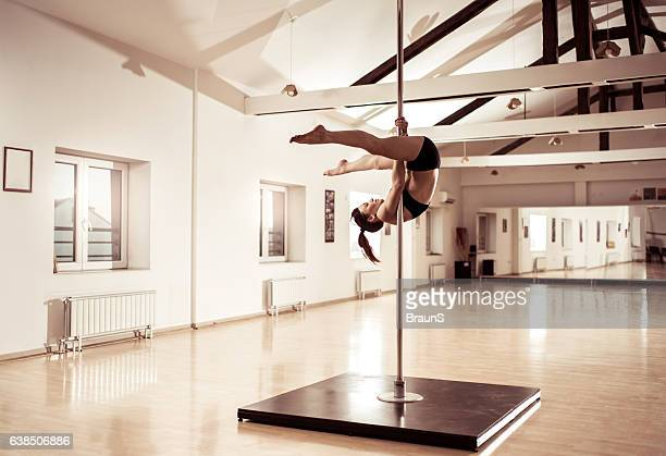 Young pole dancer exercising in a dance studio.