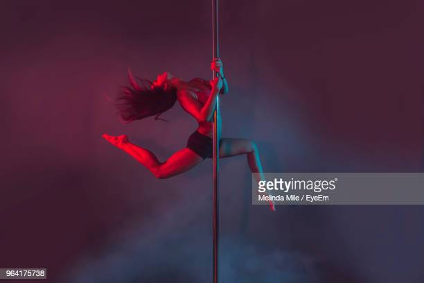 young pole dancer performing against colored background - pole dance photos et images de collection